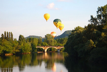 Hot air balloons over a bridge over the Dordogne valley